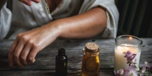 mulher com óleos e velas em cima de uma mesa para simbolizar o que é aromaterapia